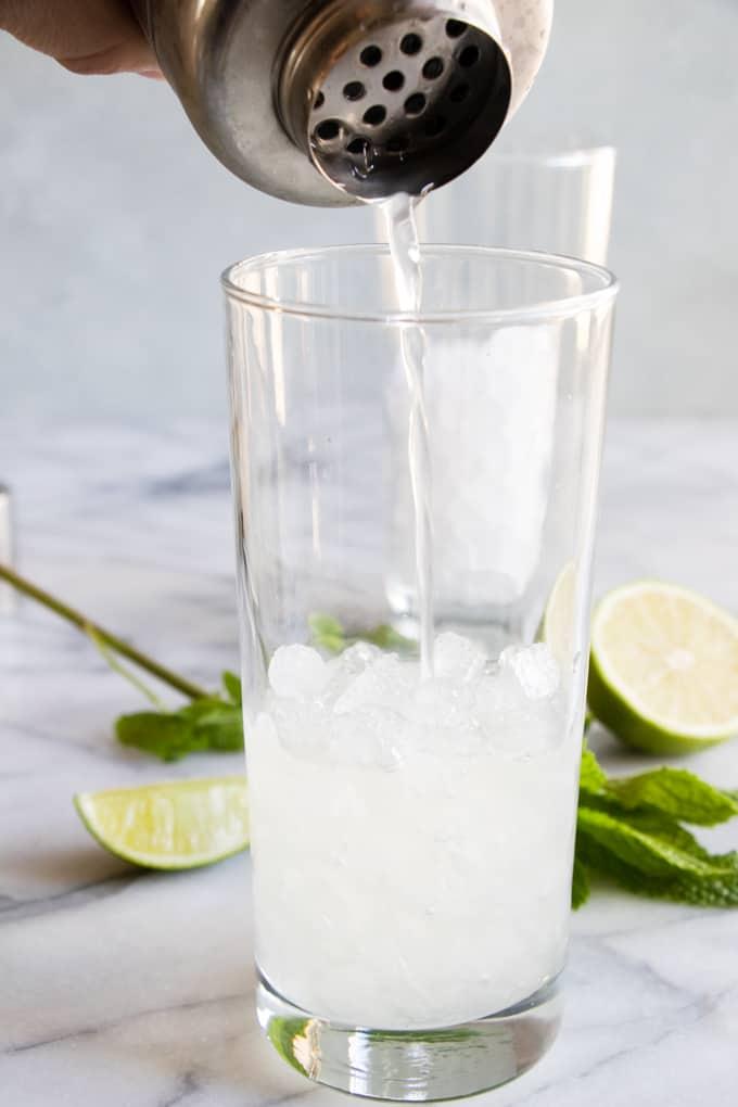 Pouring a classic mojito into a glass cup.