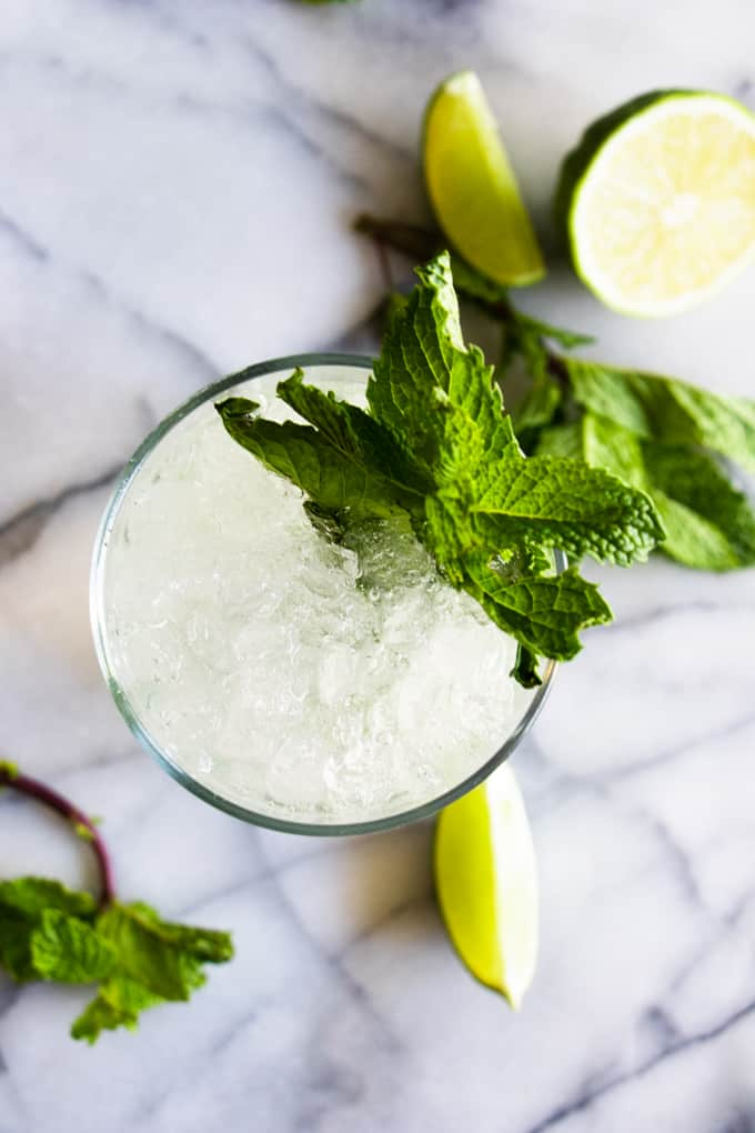 Overhead view of a classic mojito, with mint leaves and lime wedges to garnish.
