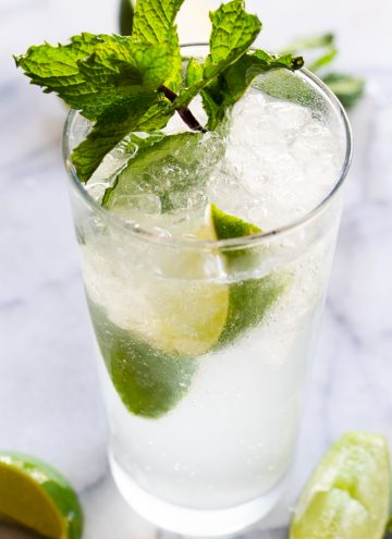 Classic mojito garnished with lime wedges and mint leaves.