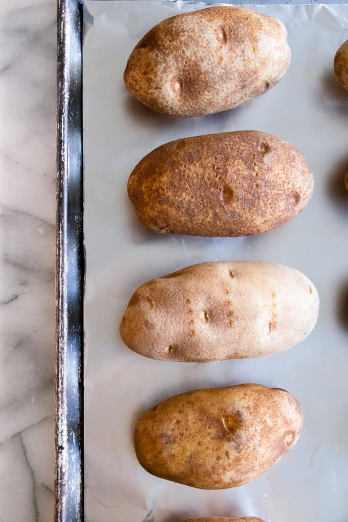 Russet potatoes lined on a baking sheet with holes poked into them to bake for twice baked potatoes.