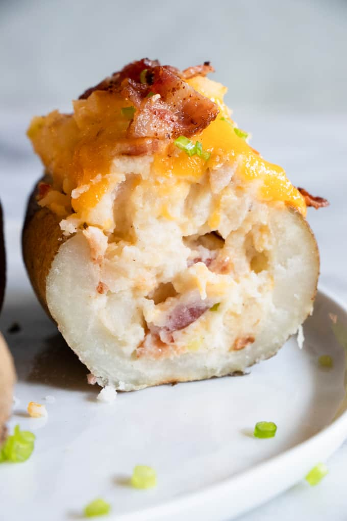 Half of a twice baked potato showing the mashed potato inside, loaded with cheese, bacon and green onion.