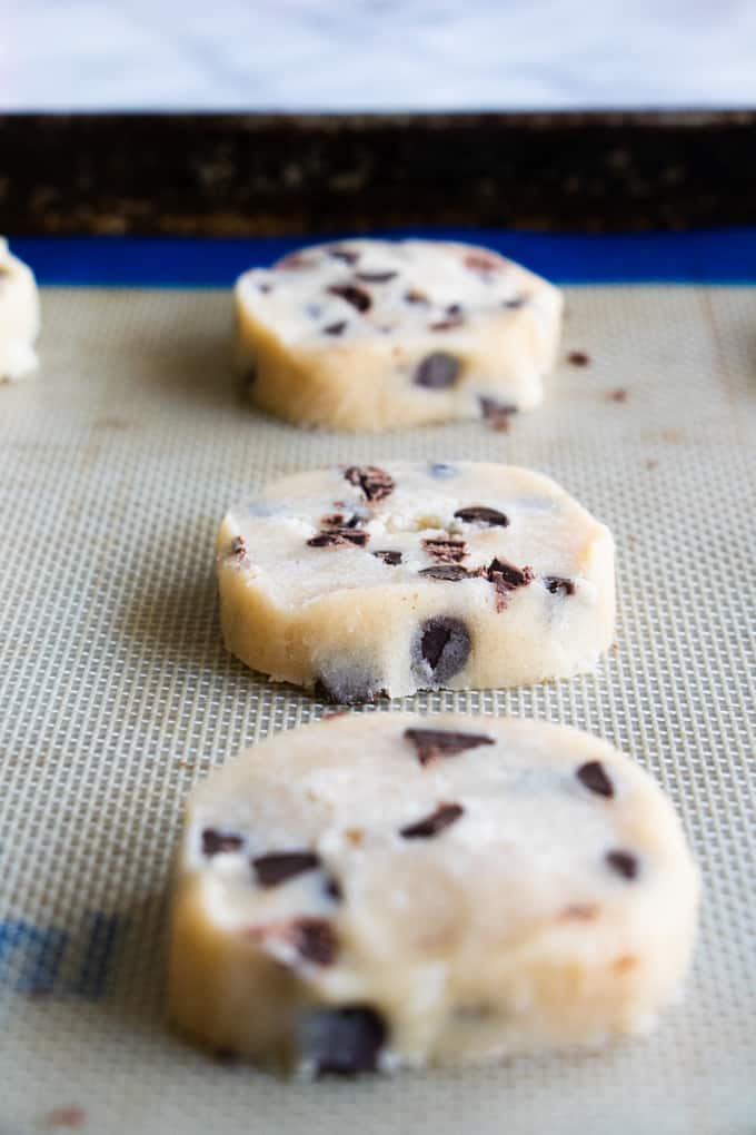 Slices of chocolate chip shortbread cookies on a baking sheet lined with a silicone baking mat.