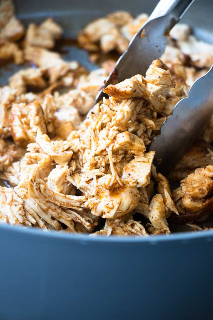 Tongs pulling up cooked, shredded chicken to pile up into tortillas for chicken tacos.