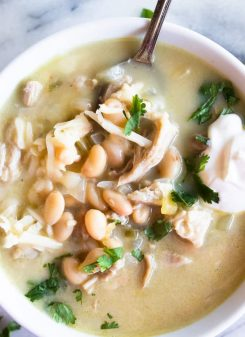 Close up image of green Chile enchilada soup, topped with sour cream and fresh cilantro.