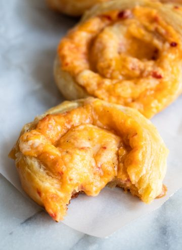 Pimento Cheese Pinwheel, with a bite missing and melty cheese oozing in the center.