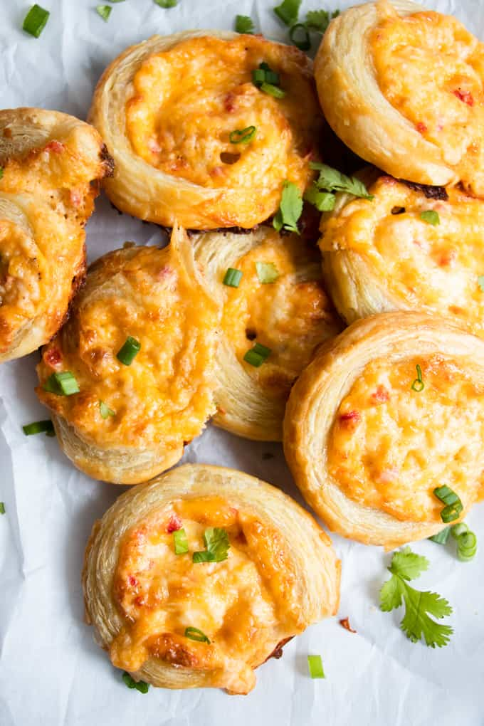 Piled up pimento cheese pinwheels garnished with green onion and cilantro.