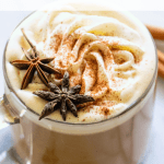 Apple spice latte topped with a swirl of whipped cream and star anise.