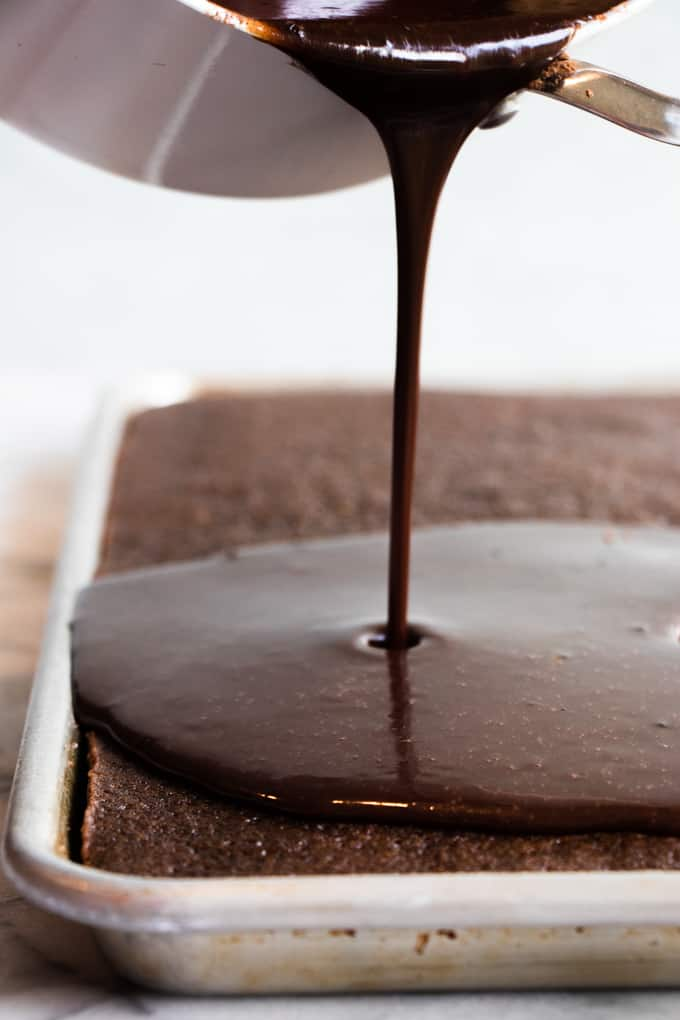 Warm chocolate icing being poured over a baked chocolate sheet cake.