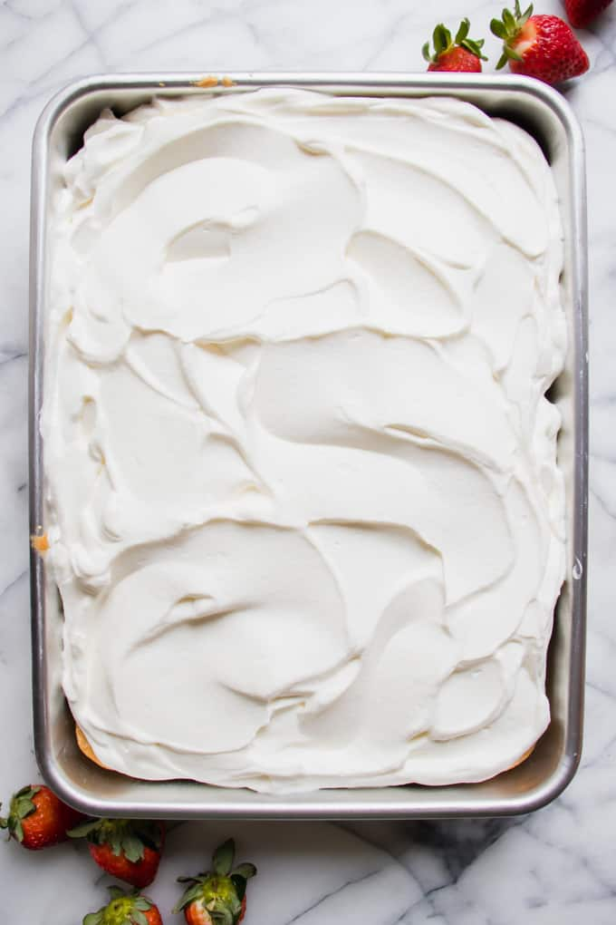 Swirls of whipped cream on top of a tres leches cake.