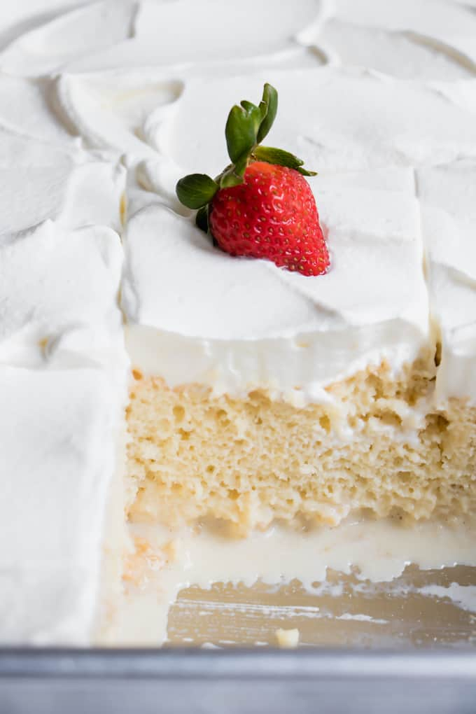 Cut tres leches cake in a cake pan showing the milk pooling at the bottom of the pan.
