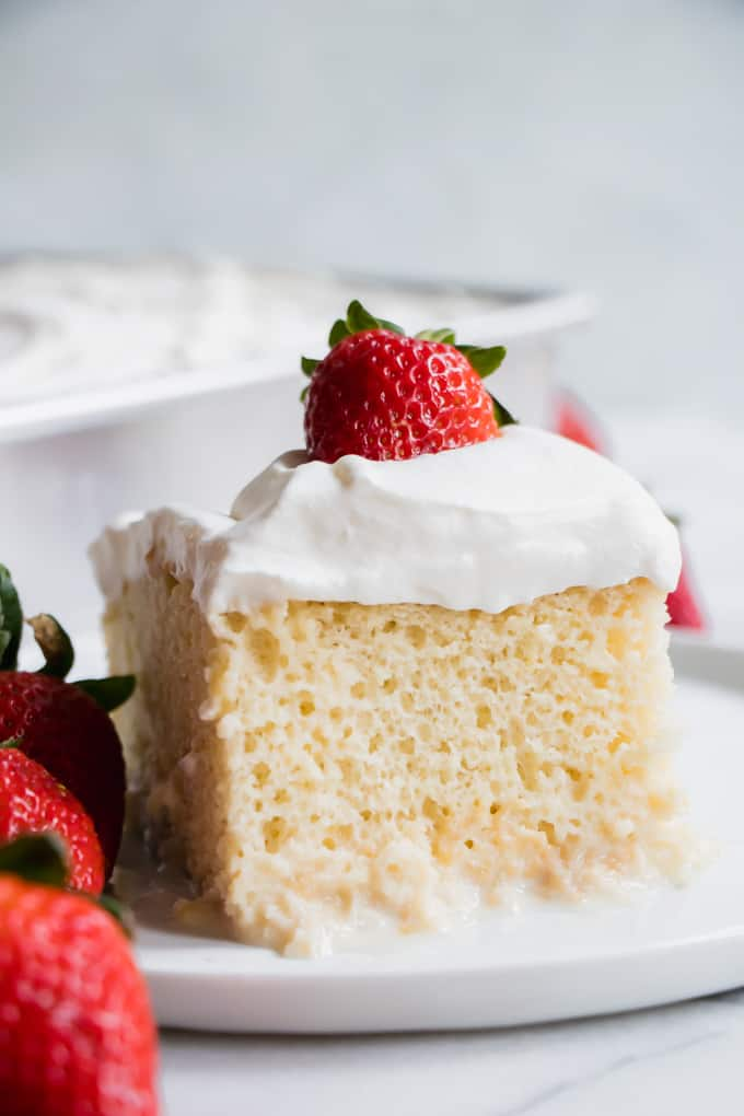 A beautifully cut out slice of tres leches cake, showing the milk pooling at the bottom of the cake.