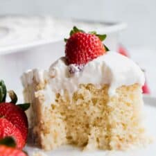 A slice of tres leches cake, topped with whipped cream and a strawberry with a bite missing.