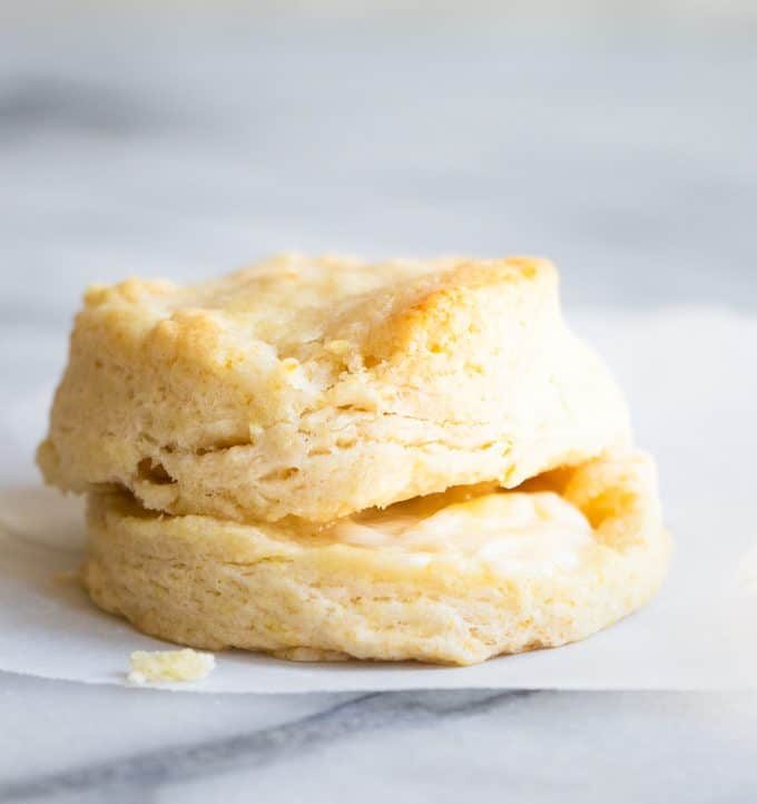 A homemade biscuit split in half, and stacked, with butter dripping out of the middle.