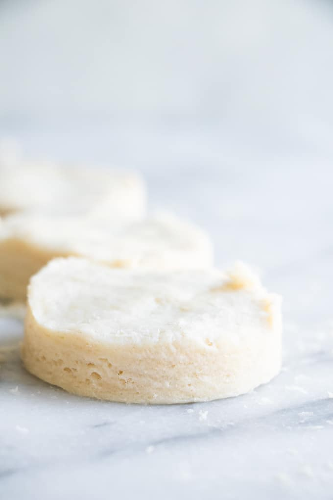 Close up image of a cut out biscuit showing the layers in the dough.
