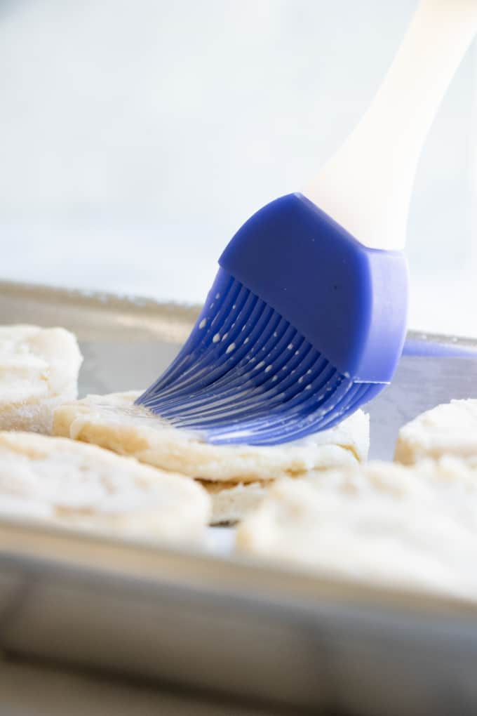 Homemade biscuit dough being brushed with cream prior to baking.
