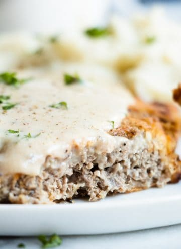 Close up image of a cut chicken fried steak showing the thick crispy coating and the tender steak inside.