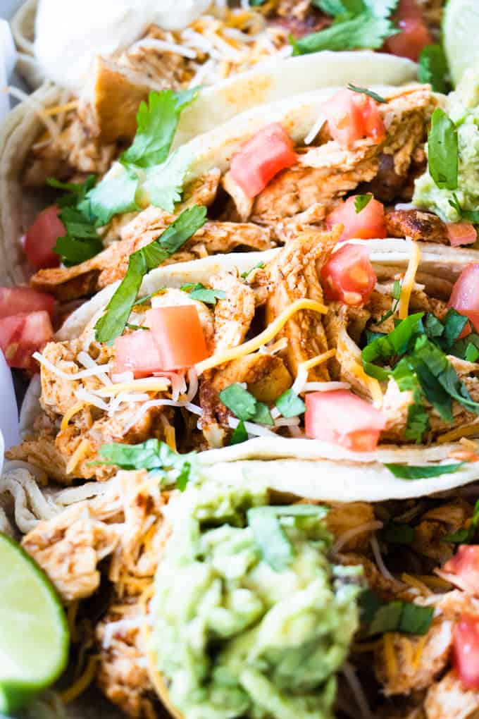 Easy shredded Mexican chicken in tacos topped with cilantro, tomatoes and cheese