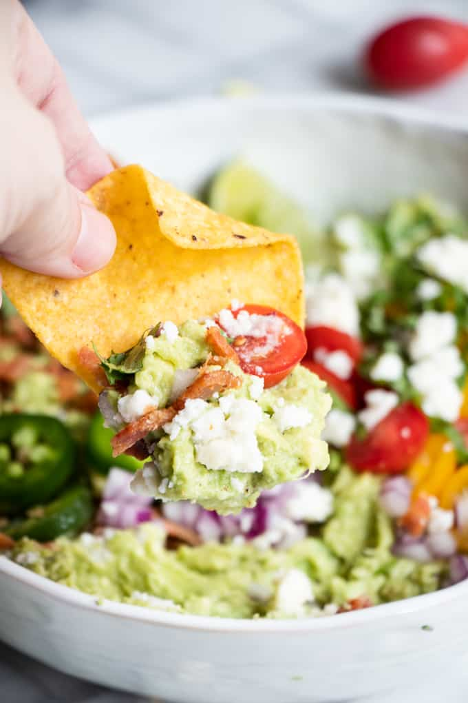 A chip dipping into loaded guacamole.