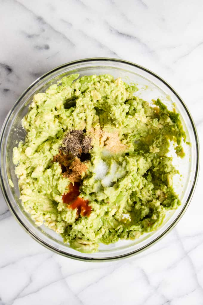Bowl of mashed avocado and spices to make homemade guacamole.