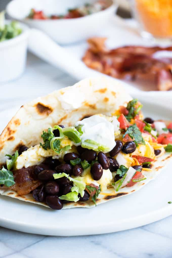 Southwest breakfast taco, flour tortilla filled with scrambled eggs, bacon, black beans, lettuce, pico, shredded cheese and sour cream.