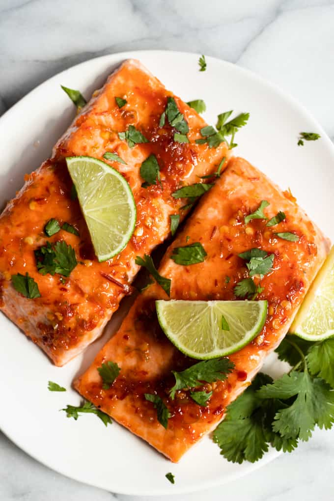 Two fillets of Chile lime salmon on a plate, garnished with lime slices and cilantro.