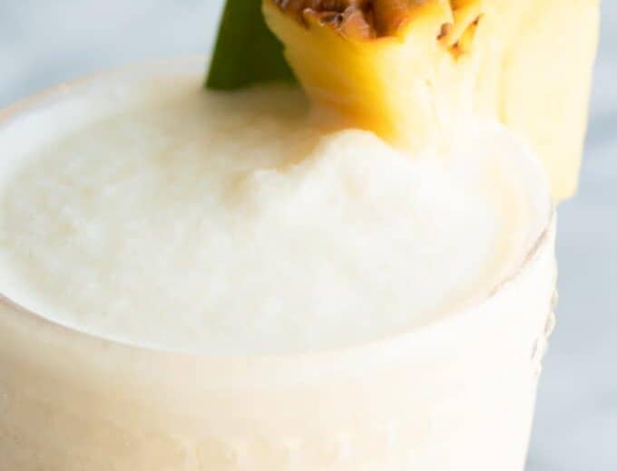 Up close of cold and frosty Pina coladas with a wedge of pineapple.