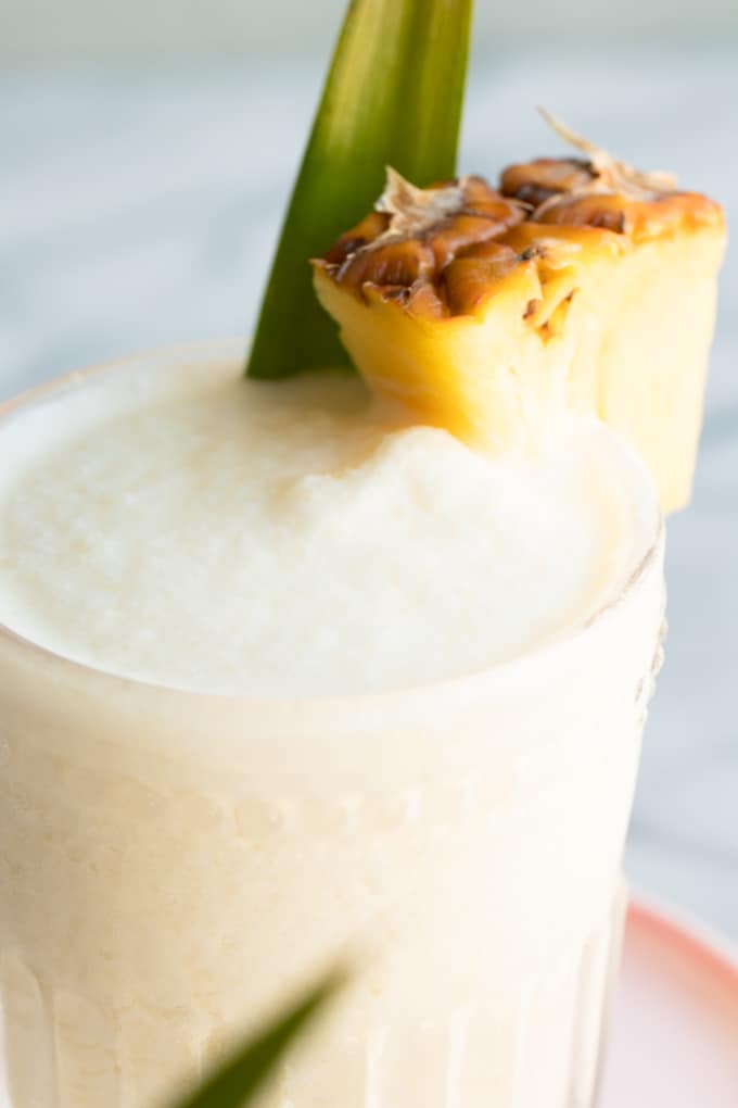 Homemade Pina Colada cocktail garnished with a pineapple slice.