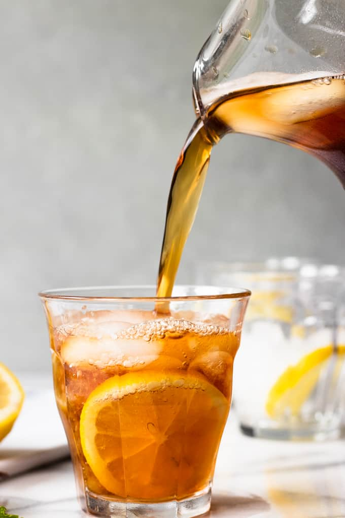 A jug pouring a glass of iced sweet tea.