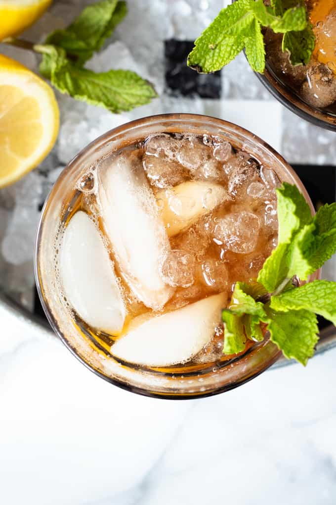 Overhead view of a glass of sweet tea with ice and a sprig of mint.