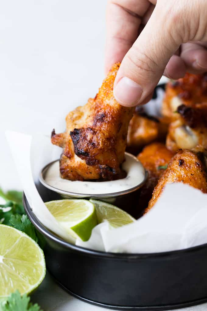 Chile Lime Chicken Wings dipping into a small cup of ranch.
