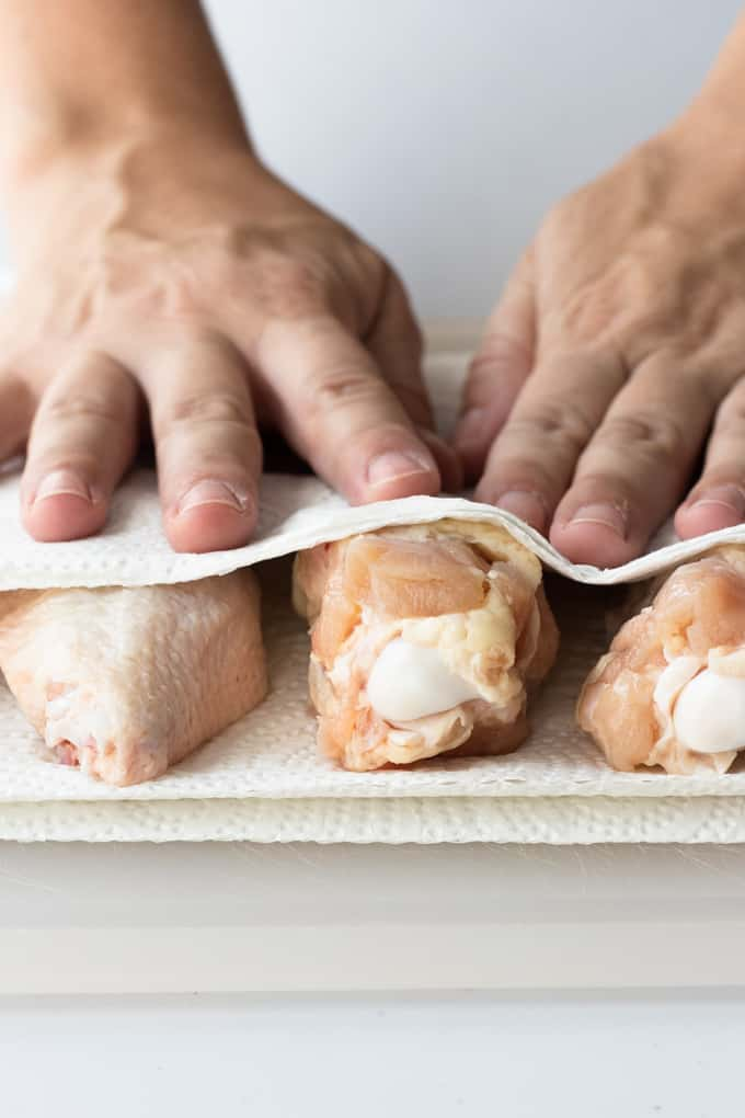 Chicken wings being pat dry with paper towels ready to make baked Chile lime chicken wings.