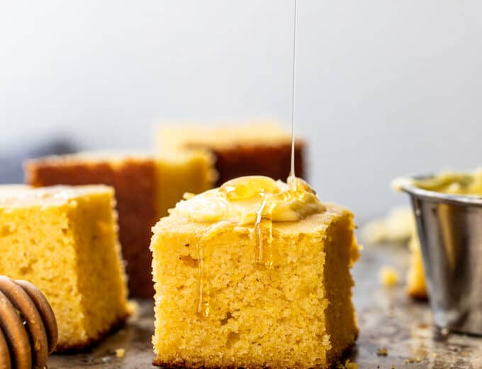 Slices of cornbread being served with butter and a drizzle of honey.