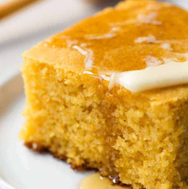 A piece of homemade buttermilk cornbread topped with butter and dripping with honey.