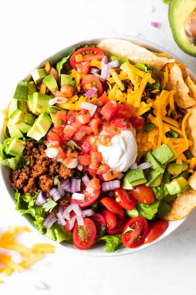 Taco salad showing all the toppings, ground taco meat, avocado, tomatoes, cheese, sour cream, salsa and tortilla chips.