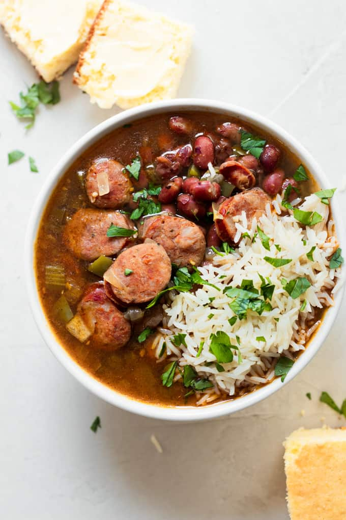 A bowl filled with red beans and rice, chunks of corn bread on the side.