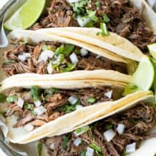 Slow cooked beef barbacoa loaded onto soft warm corn tortillas.