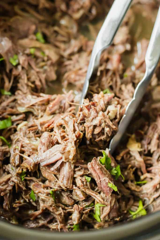 Shredded beef barbacoa in a slow cooker.