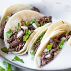 Slow cooker barbacoa loaded into white corn tortillas for street tacos.
