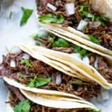 Slow cooker barbacoa street tacos lined up and topped with cilantro and diced onion.