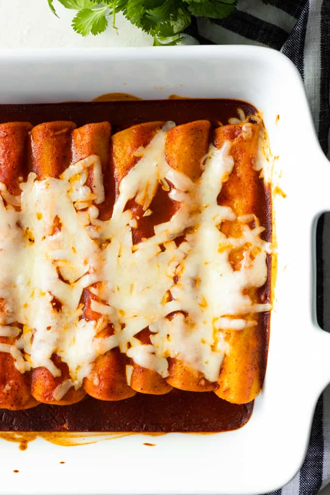 Baking dish filled with baked beef enchiladas topped with melted cheese.