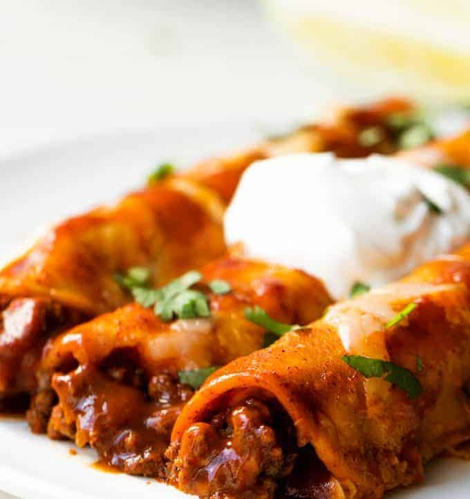 Homemade Beef Enchiladas served on a plate with diced cilantro and a swirl of sour cream on top.