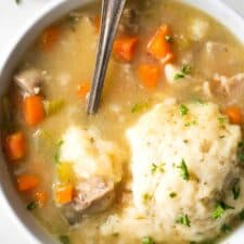A bowl of chicken and dumplings, with a spoon digging in.