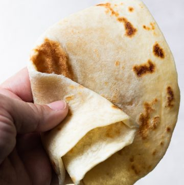 A hand holding and folding a homemade flour tortilla.
