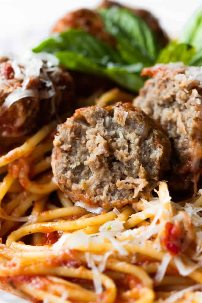 Cut open meatball on a plate of spaghetti and meatballs.
