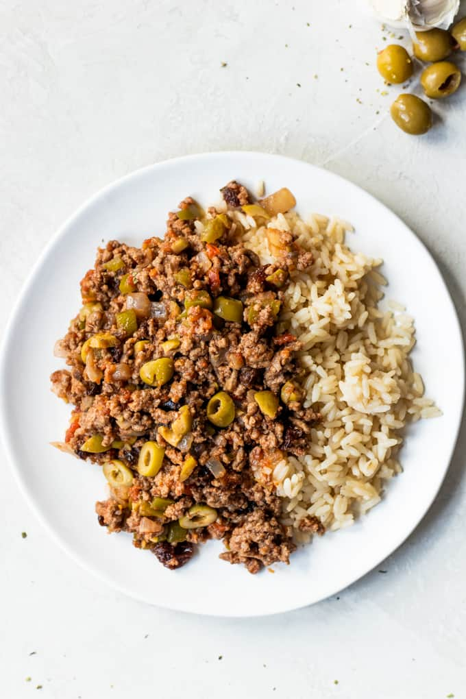 Picadillo on a white plate and garnished with green olives.