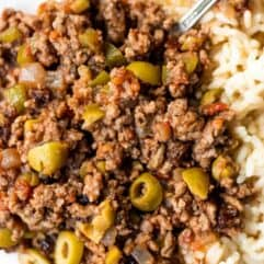 Homemade cuban picadillo served over white rice and served with a fork.