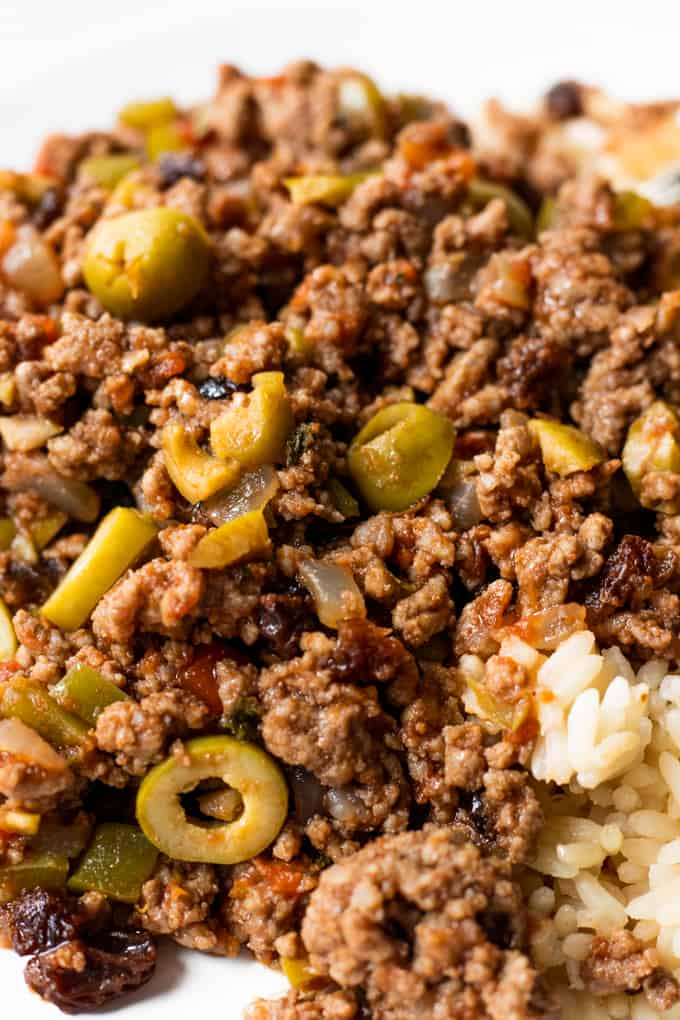 Close up of picadillo showing sliced green olives and raisins mixed with the ground beef.