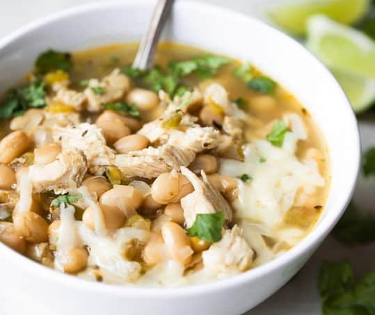 Bowl of white chicken chili served with a spoon.