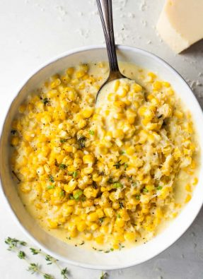 White bowl filled with cream corn, serving spoon, off to the side is a wedge of parmesan cheese.