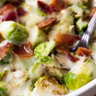 Baked Creamy Brussels sprouts in a baking dish with a spoon scooping up.
